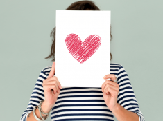 Woman holding red heart drawing on white paper